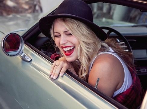 Женщина сидит в новом автомобиле и улыбается