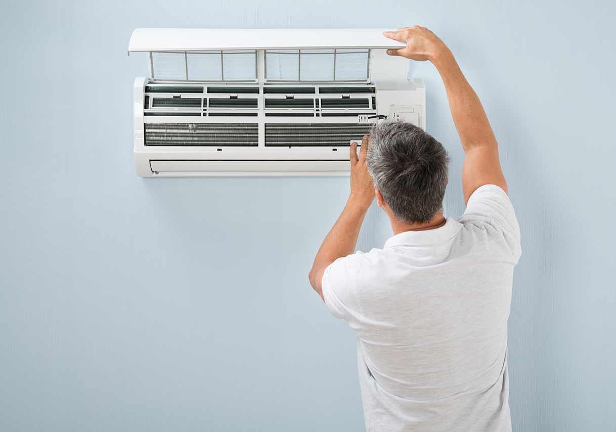 man-inspecting-air-conditioning-unit.jpg